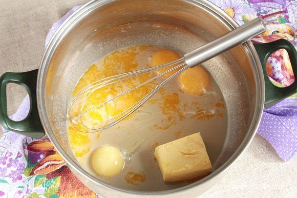 Добавить яичные куриные желтки (4 шт.) и масло сливочное (90 г) комнатной температуры. Тщательно перемешать, слегка взбивая венчиком.