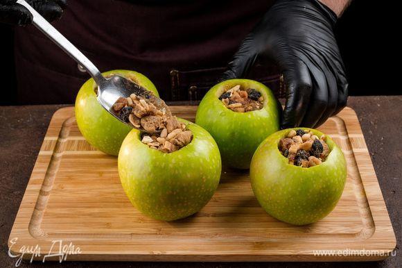 Нафаршируйте яблоки плотно смесью сухофруктов и орехов. Каждое яблоко заверните в фольгу, оставив сверху небольшое отверстие. Запекайте 35 минут при 180°С.