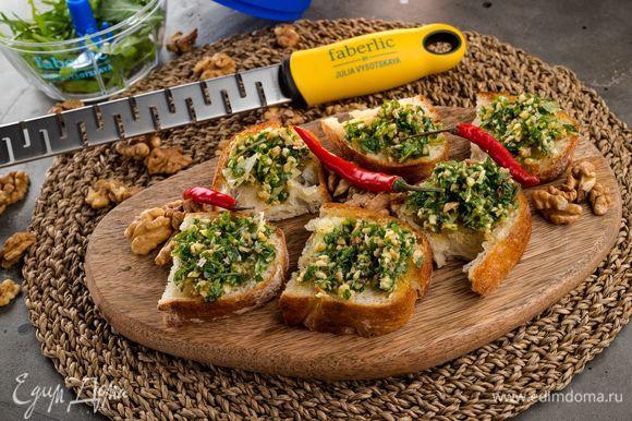 Намажьте брускетты соусом песто, посыпьте оставшимся сыром. Приятного аппетита!
