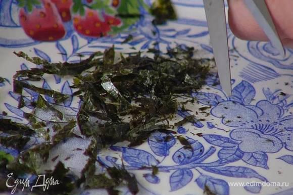 Листы нори сложить в несколько раз и нарезать ножницами мелкой соломкой.