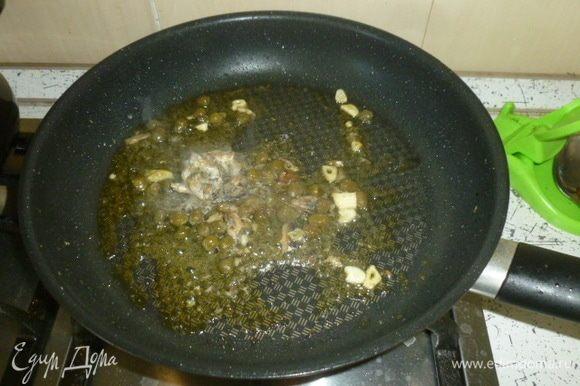 Спагетти отварить в подсоленной воде до состояния аль денте, откинуть на дуршлаг (сохранить немного воды от варки). В большой сковороде или сотейнике разогреть масло, пропустить через пресс чеснок, добавить анчоусы и каперсы.