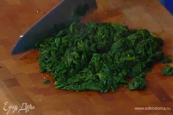 Приготовить начинку: шпинат опустить на 2‒3 минуты в кипящую воду, откинуть на дуршлаг, дать стечь лишней воде и промокнуть шпинат бумажным полотенцем, затем мелко порубить и немного остудить.