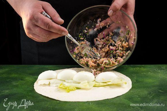 Собираем роллы. Расстелите лаваш, выложите на него салатные листья. Сверху положите несколько ложек салата и дольки яиц.