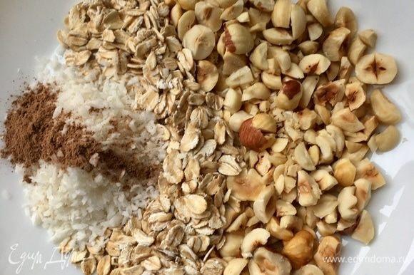 В миске смешать овсяные хлопья, порубленный фундук, кокосовую стружку и корицу.