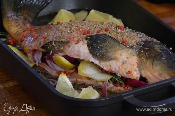 Влить в сотейник с рыбой вино и 300 мл воды, выложить цедру и кусочки лимона, накрыть крышкой и томить до готовности 30‒35 минут.