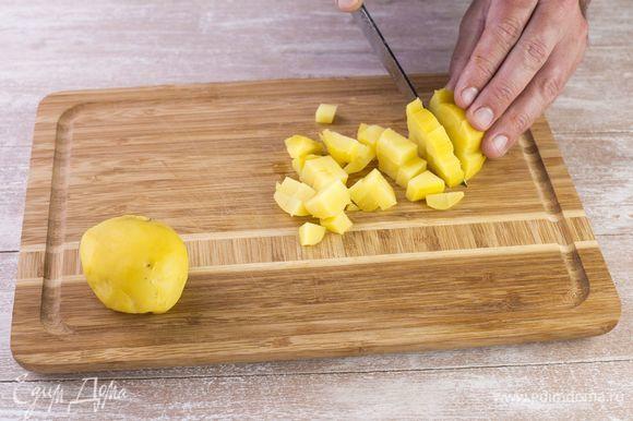 Сварите картофель в мундире, очистите от кожуры и нарежьте мелким кубиком.