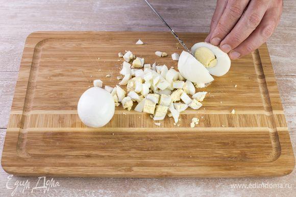 Сварите яйца вкрутую, очистите от скорлупы, нарежьте мелким кубиком.