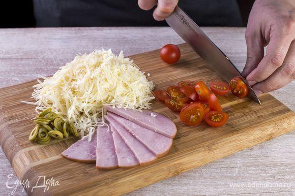 Нарежьте тонкими полосками ветчину. Натрите на крупной терке сыр. Порубите оливки колечками, а черри — кружками.