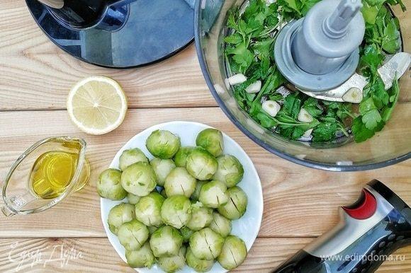 С брюссельской капусты снимаем верхние темно-зеленые листочки, обрезаем плодоножку и делаем надрезы крест-накрест. Этот шаг позволит на 100 % избавиться от горечи и даст маринаду пропитать капусту. Делаем маринад: в чашу блендера кладем 25 г петрушки, 3 зубчика чеснока, наливаем 2 ст. л. оливкового масла и 1 ч. л. лимонного сока. Включаем блендер на полную мощность и тщательно все перемалываем.