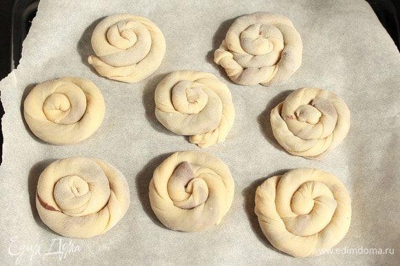 Колбаски слегка покрутить в жгутики и свернуть спиральками. Кончик заправить под спиральку. Выложить на застеленный пергаментом противень.