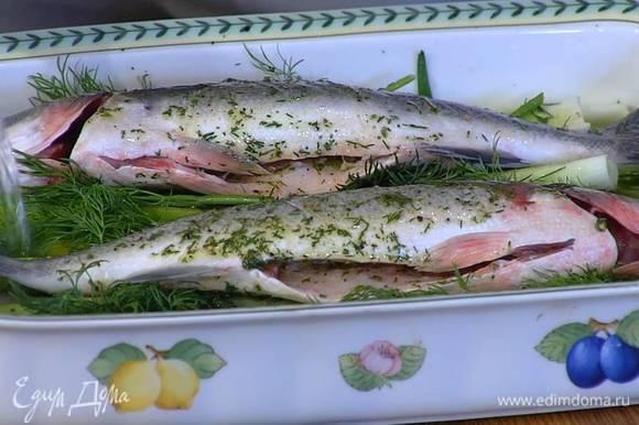 На сибасе сделать с двух сторон неглубокие надрезы и смазать тушки пряной смесью, в форму рядом с рыбой влить вино, затянуть сверху фольгой и отправить в разогретую духовку на 10 минут, затем снять фольгу и запекать рыбу еще 10 минут.