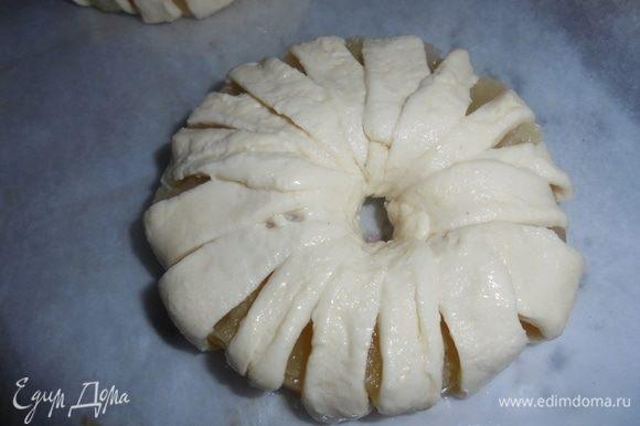 Каждое колечко ананаса ТМ «Фрау Марта» обмотать ленточками слоеного теста и выложить на противень, смазанный маслом.