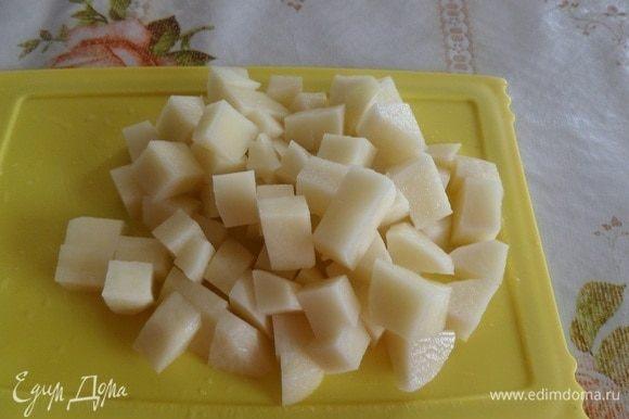 Пока варится мясо, очищаем и нарезаем кубиком картофель.