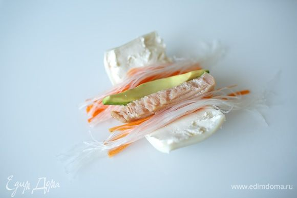 Кладем на подготовленный кусочек кальмара фунчозу, морковь, дольку авокадо и брусочек тунца.