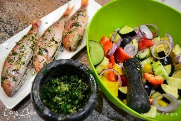 Готовим маринад для рыбы и овощей: имбирь, чеснок мелко натираем и в ступку. Туда же — измельченную зелень и специи. Все хорошенько растолочь, добавить масло, сок лимона. Из нескольких ароматов создаем один! Все хорошенько перемешиваем. Барабульку хорошенько со всех сторон обмазываем соусом и оставляем на 30 минут. А в это время нарезать овощи и полить соусом, как и для рыбы, дать пропитаться.