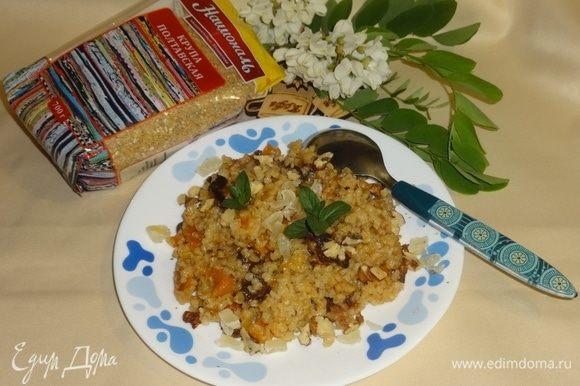 Выложить порцию каши в тарелку. Посыпать орехами и цукатами. Украсить листиками мяты.