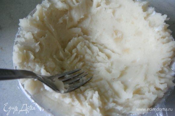 Берем небольшой салатник, застилаем его пищевой пленкой, так чтобы концы немного свисали. Выкладываем примерно 5 ст. л. картофеля и распределяем его по дну и стенкам.