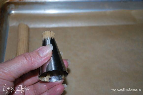 Через насадку «открытая звезда» формируем печенье-палочки и выкладываем их на пергамент.