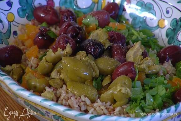 Готовый рис выложить на блюдо, сверху разложить курагу и оливки, посыпать все измельченной зеленью, сбрызнуть оливковым маслом, посолить и поперчить.