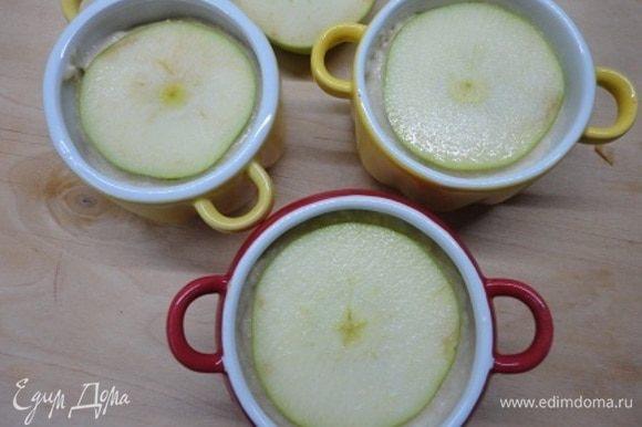 Разложите по формочкам. Сверху прикройте тоненькими колечками яблока. Выпекайте в духовке 20 минут при 200°C.