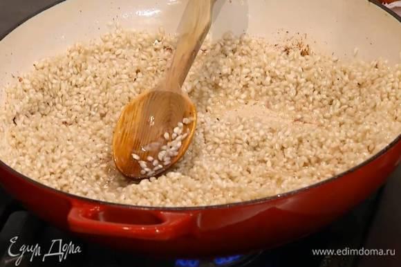 В сотейник с маслом всыпать рис и сделать тостатуру: прогревать, постоянно помешивая, 1–2 минуты, пока рис не станет прозрачным.