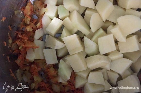 Как только лук стал прозрачным, а морковь мягче, добавляем в кастрюлю картофель, нарезанный кубиками. Перемешиваем, пару минут держим на огне и заливаем бульоном или бутилированной водой. Варить около 15 минут.