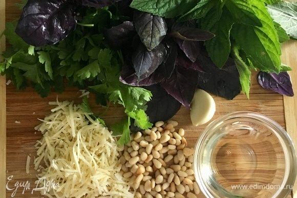 Сделаем соус песто для верха пирога. Для него берем по пучку базилика, петрушки и мяты. Зубчик чеснока. Горсть обжаренных кедровых орешков и немного натертого пармезана. Оливковое масло. Все ингредиенты взбить в блендере, посолить и поперчить немного.