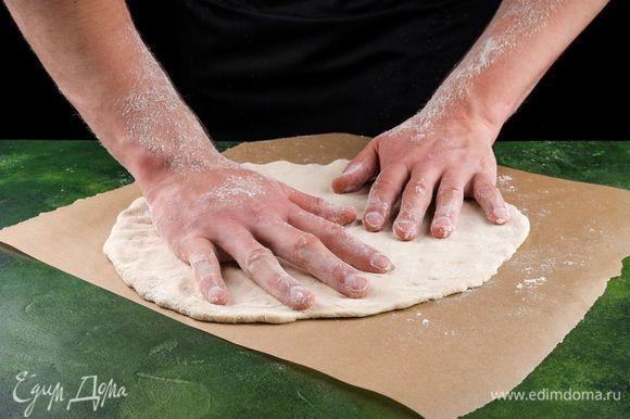 Когда тесто подойдет, раскатайте его в круглый пласт.