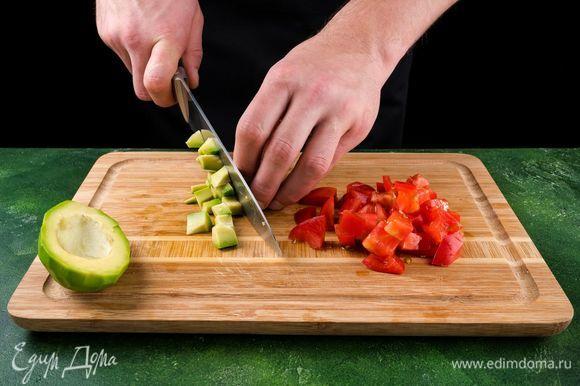 Помидор разрежьте на 4 части, очистите от семян. Нарежьте мелкими кубиками. Добавьте к измельченной смеси. Авокадо почистите, нарежьте кубиками.