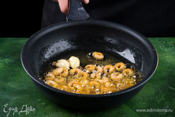 Разморозьте креветки и очистите их. В большой сковороде растопите 2 ст. л. сливочного масла и смешайте с 2 ст. л. оливкового масла. Добавьте измельченный чеснок и красный перец и обжарьте креветки приблизительно от 3 до 5 минут.