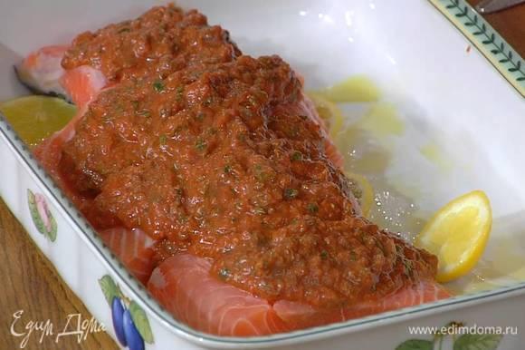 Жаропрочную керамическую форму сбрызнуть оливковым маслом, выложить кружки лимона, сверху поместить семгу и залить все красным песто.