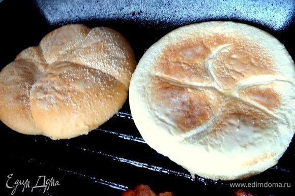 Рядом с беконом обжарить половинки булочки для гамбургеров.