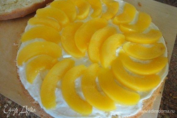 Для пропитки 50 мл сиропа от персиков смешайте с лимончелло и пропитайте бисквит, разрезанный на два коржа. Смажьте один корж половиной крема и выложите большую часть долек персиков.