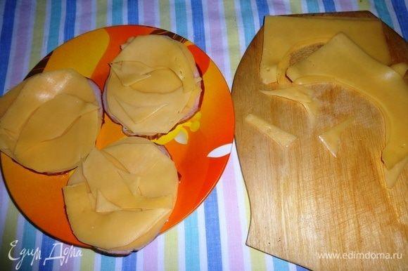 Уложить полукруги сыра на кружок карбонада. Так поступить со всеми кружками. Из оставшихся частей сыра вырезать различные округлые фигуры и также уложить их на кружки карбонада.