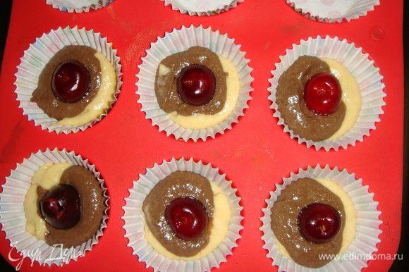 В формы для кексов вложить бумажные капсулы. Выкладываем тесто чайной ложкой, чередуя темное и светлое. В середину положить по одной черешне без косточки.