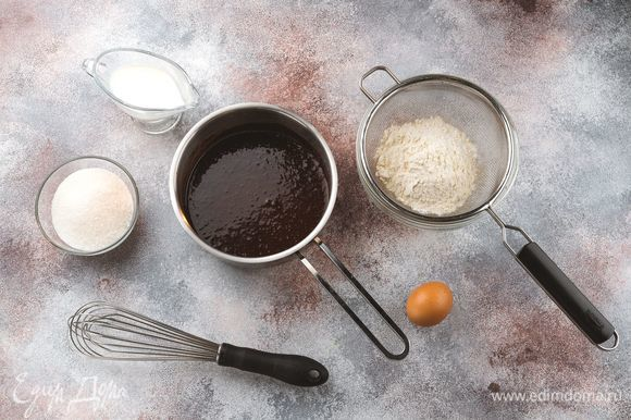 К полученной массе добавьте яйцо, сахар, просеянную пшеничную муку и оставшееся молоко. Снова тщательно перемешайте.
