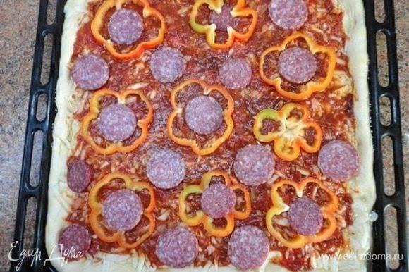 Покройте кружочками перца и салями. В оригинальном рецепте указывалось 12 кусочков салями, но нашлось много помощников и советчиков, которые вначале пробовали салями, а потом сказали, что колбасой пиццу не испортишь и потребовали выложить побольше кружочков, добавили еще и несколько кусочков чоризо.