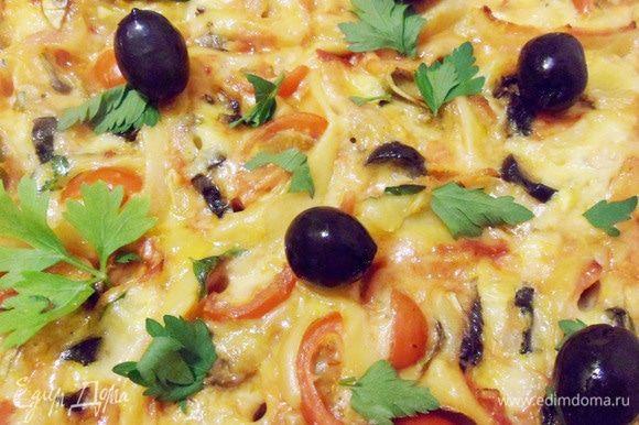 Готовую пиццу можно украсить зеленью, маслинами и помидорами черри.