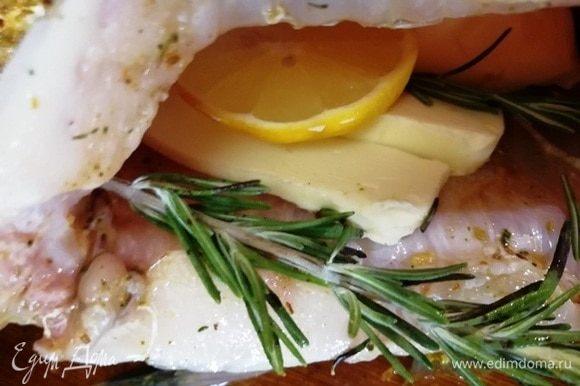 В брюшко укладываем сливочное масло, дольку лимона, веточки розмарина.