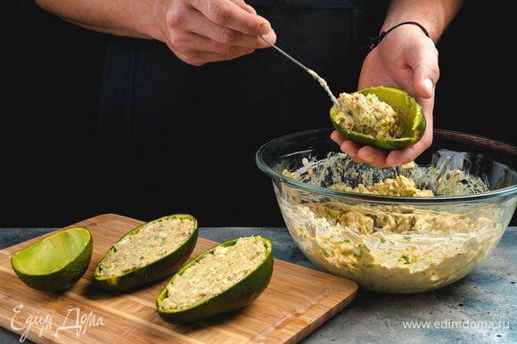 Наполните половинки авокадо салатом и украсьте зеленью.