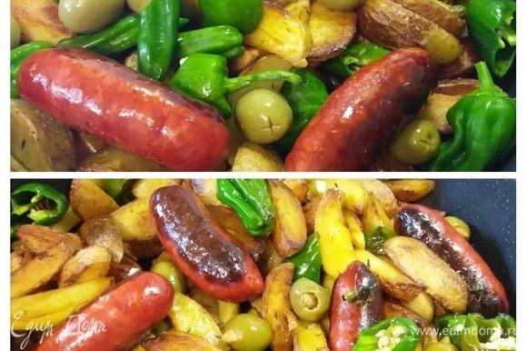Выложить в картофель колбаски, перцы, маслины и каперсы. Обжарить все вместе в течение еще нескольких минут, колбаски должны прогреться. В самом конце добавить мелко нарезанный зубчик чеснока.