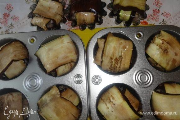 Таким образом сделать все остальные фрикадельки. Формочки смазать растительным маслом и положить в них фрикадельки в баклажанах стыками вниз. В каждую формочку налить по 2 ст. ложки воды.