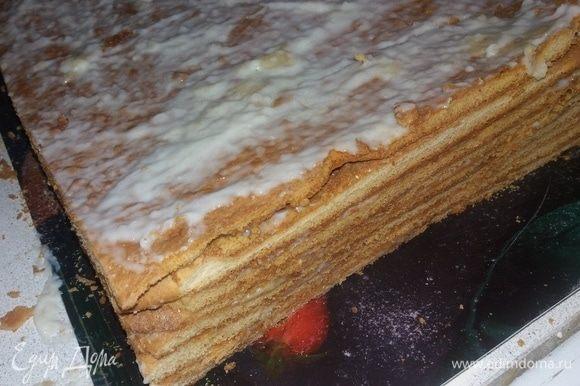 Обильно смазать остывшие коржи кремом. Ножом придать форму торту. Смазать кремом края.
