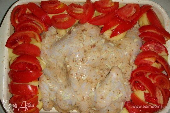 Помидоры тоже режем дольками и выкладываем поверх картофеля, солим. Чеснок мелко режем и посыпаем курицу. Форму накрываем фольгой и ставим в разогретую до 200°C духовку. Через 40 минут снимаем фольгу и посыпаем натертым сыром. Запекаем еще минут 20–30.