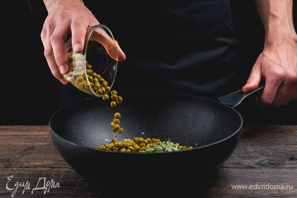 Далее добавьте зеленый горошек. Приправьте овощи солью и перцем, положите мелко нашинкованную зелень.