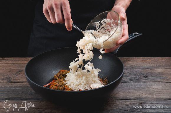 Выложите в сковороду отварной рис, хорошо перемешайте, накройте крышкой и выдержите на огне минуту.