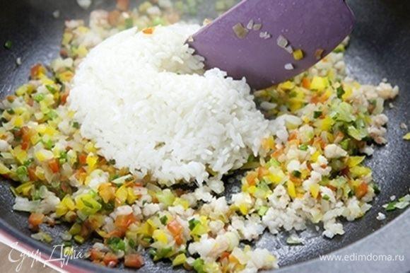 Выложите рис на сковороду и хорошо перемешайте.