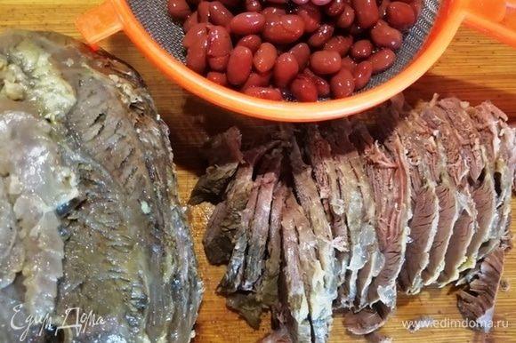 Сольем жидкость из консервированной фасоли, говядину нарежем тонкими пластинками. Мелко нарезать говядину не советую, она — главный ингредиент в салате.