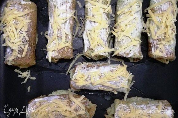 Выкладываем подготовленные блинчики на противень. Смазываем сметаной, посыпаем сыром.