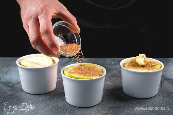 Сверху выложите яблочные дольки. Посыпьте яблоки коричневым сахаром и положите пару кусочков сливочного масла.